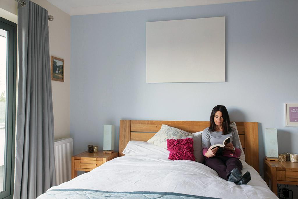 Heat4All ICONIC Classic infraroodverwarming aan de muur achter het bed. Getoond model: 600 Watt - 90 x 70 cm.