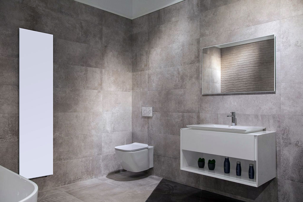 Wit infraroodpaneel aan de muur in de badkamer. Verticaal gemonteerd. Model Classic 820 (170 x 40 cm). Boven de wastafel een Spiegel infraroodpaneel (model Spiegel 540, 80 x 60 cm)