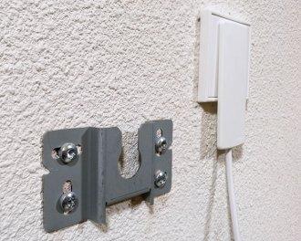 De platte stekker past in een stopcontact dat achter het infraroodpaneel verwerkt is. Links een van de twee montagebeugels